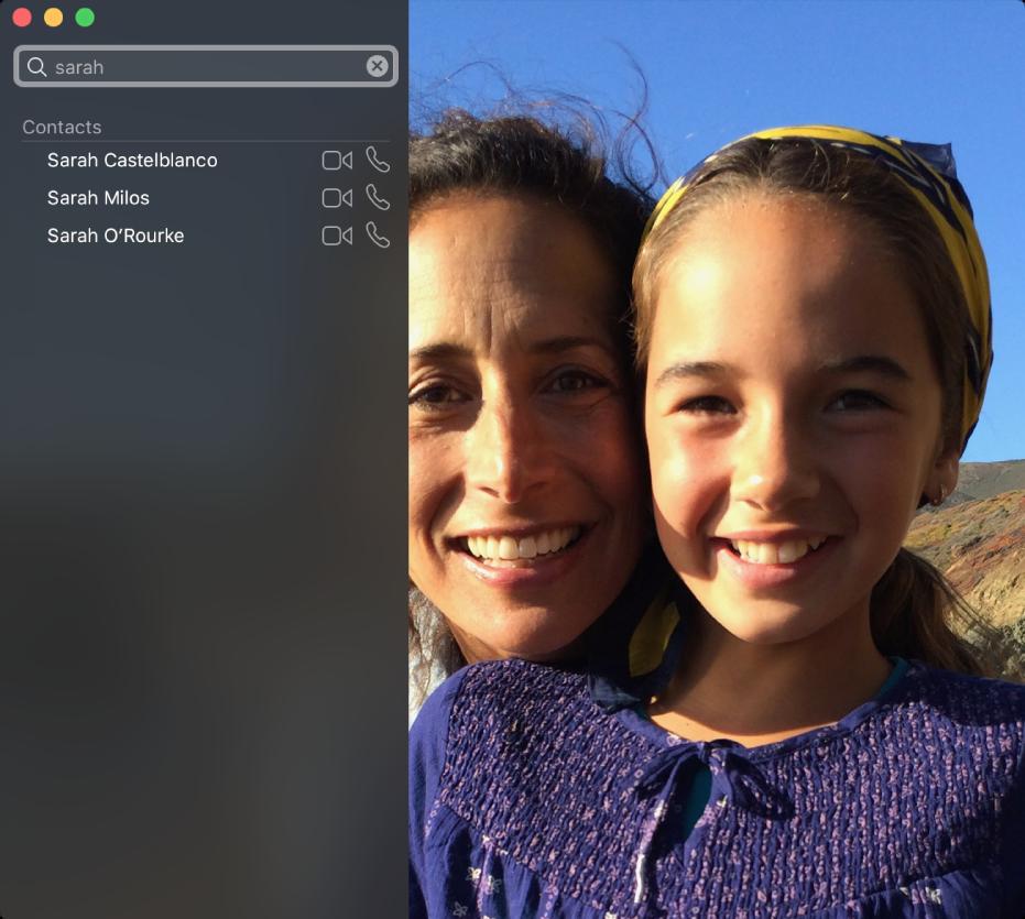 """Okno FaceTime před zahájením hovoru. Vlevo nahoře je pole hledání se zadaným slovem """"Sarah"""". Pod ním je seznam výsledků hledání, vněmž jsou uvedeny kontakty jménem Sarah. Vedle každého znich je tlačítko, pomocí nějž lze zahájit videohovor nebo audiohovor. Vpravo je obraz zvaší kamery – dva lidé připraveni zahájit hovor."""