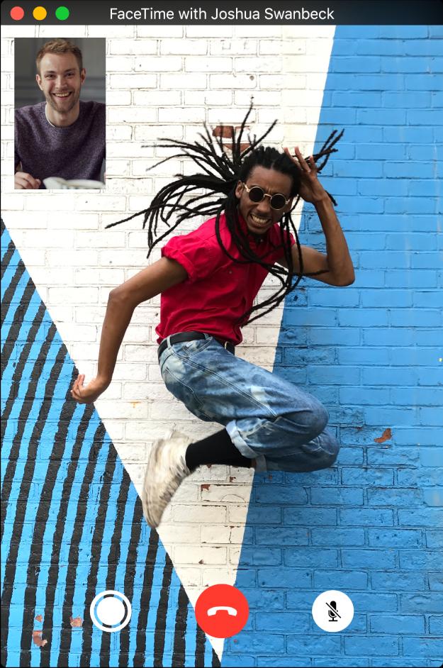 In het FaceTime-venster zie je een springende man die een videogesprek voert met een andere man. Onder in het FaceTime-venster staan drie knoppen: de Live Photo-knop, waarop de man kan klikken om een Live Photo van het moment te maken, en de knoppen om het gesprek te beëindigen of het geluid uit te zetten.