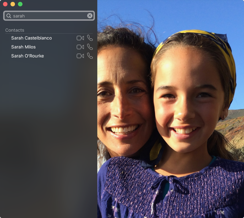 """Okno FaceTime przed nawiązaniem połączenia. Wlewym górnym rogu znajduje się pole wyszukiwania, awnim wpisane słowo """"Sarah"""". Poniżej widoczny jest wynik wyszukiwania zkontaktami oimieniu Sarah, oraz przyciskami obok, pozwalającymi rozpocząć połączenie wideo lub audio. Po prawej kamera pokazuje dwie osoby gotowe do nawiązania połączenia."""