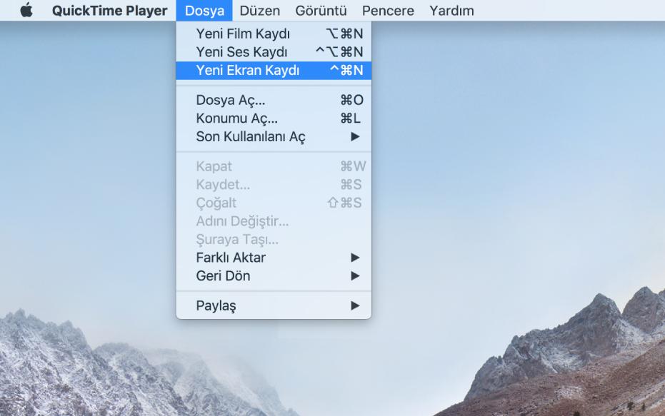 Kullanıcı Dosya > Yeni Ekran Kaydı'nı seçip, Kayıt Yap'ı tıklayıp, ekranın bir bölümüne doğru sürükleyip Kaydı Başlat düğmesini tıkladıktan sonra ekran kaydını gösteren bir Mac ekranı. Ekranın seçilen bölümü imlecin Finder Düzen menüsündeki Emoji ve Semboller öğesini tıkladığını gösterir.