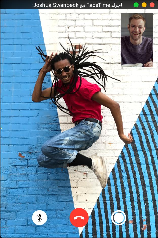 نافذة FaceTime يظهر بها رجل يقفز أثناء إجراء مكالمة فيديو مع رجل آخر. الجزء السفلي من نافذة FaceTime ويعرض ثلاثة أزرار: زر LivePhoto، الذي يمكن للشخص النقر عليه لالتقاط LivePhoto للّحظة، وزر إنهاء المكالمة وزر كتم الصوت.