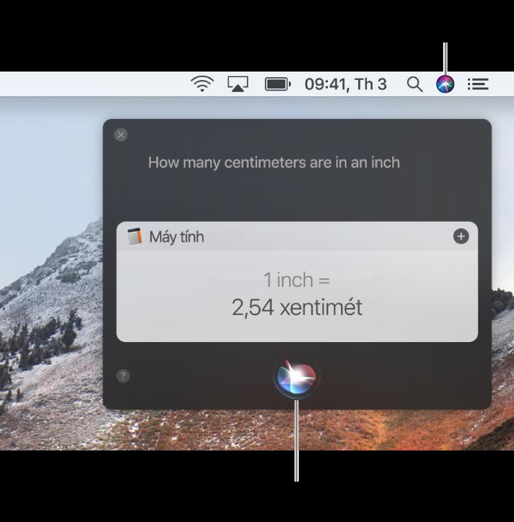 """Phần trên cùng bên phải của màn hình nền trên máy Mac đang hiển thị biểu tượng Siri trên thanh menu và cửa sổ Siri với yêu cầu """"How many centimeters are in an inch"""" và câu trả lời (chuyển đổi từ Máy tính). Bấm vào biểu tượng ở chính giữa trên cùng của cửa sổ Siri để thực hiện một yêu cầu khác."""