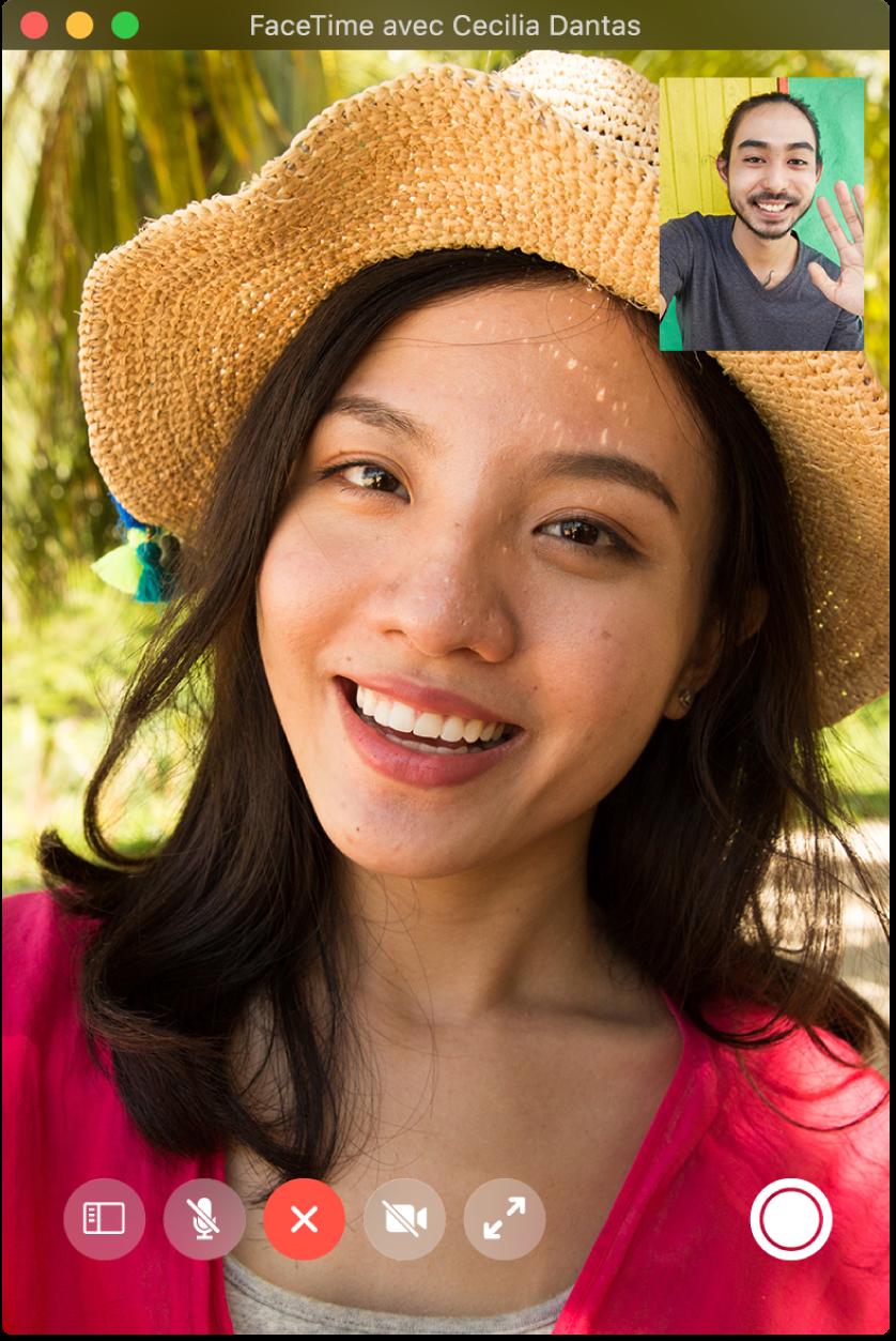 La fenêtre FaceTime présentant deux personnes pendant un appel; l'appelant est affiché dans la fenêtre d'image dans l'image dans le coin supérieur droit. Dans le coin inférieur droit se trouve le bouton LivePhoto, sur lequel chacun des correspondants peut cliquer afin de prendre une LivePhoto du moment.