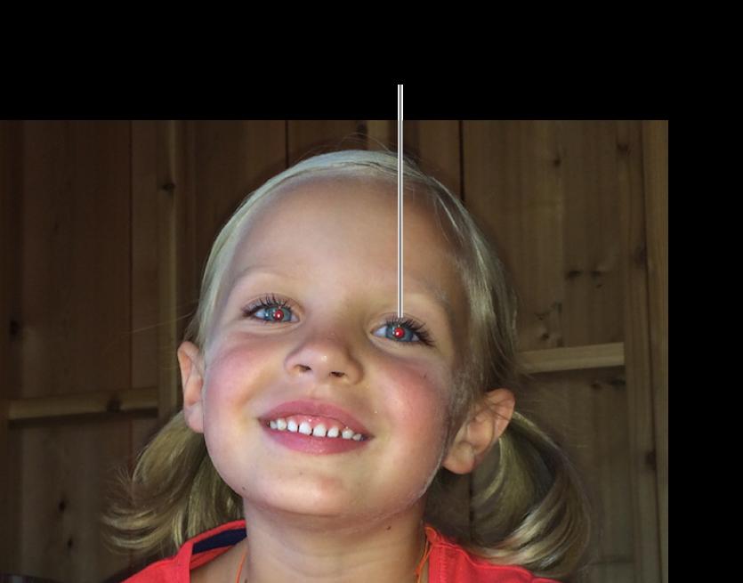 Una foto de un niño con las pupilas rojas.
