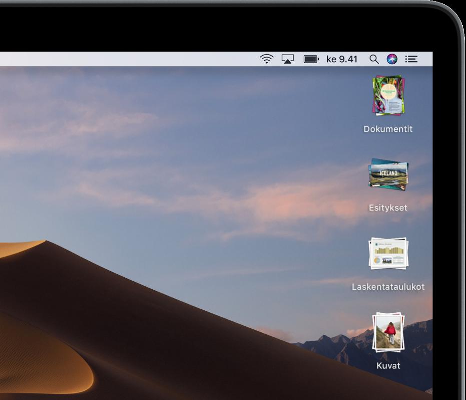 Macin työpöytä, jonka oikeassa reunassa on pinoja.