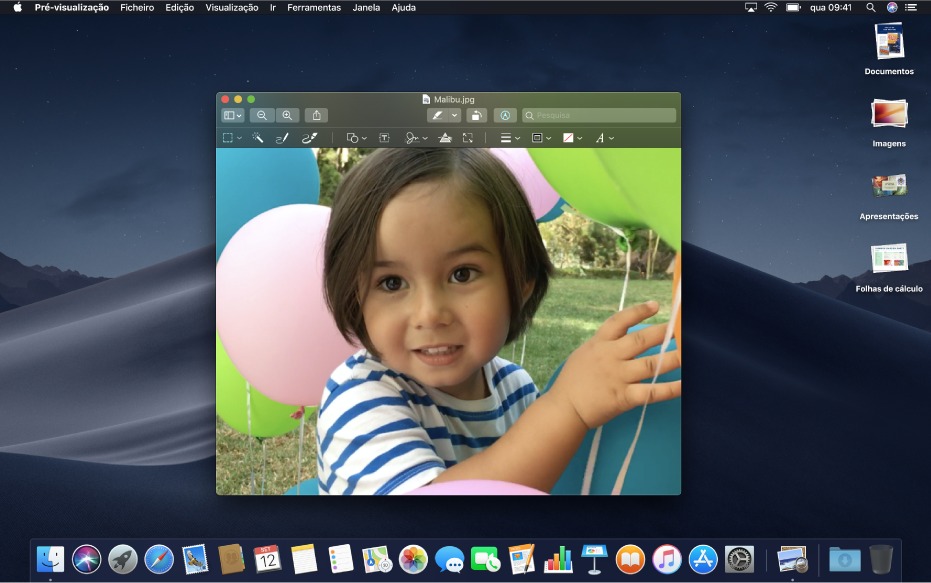 Uma secretária de Mac definida para o modo escuro, a mostrar uma janela de aplicação, a Dock e a barra de menus em versão escura.