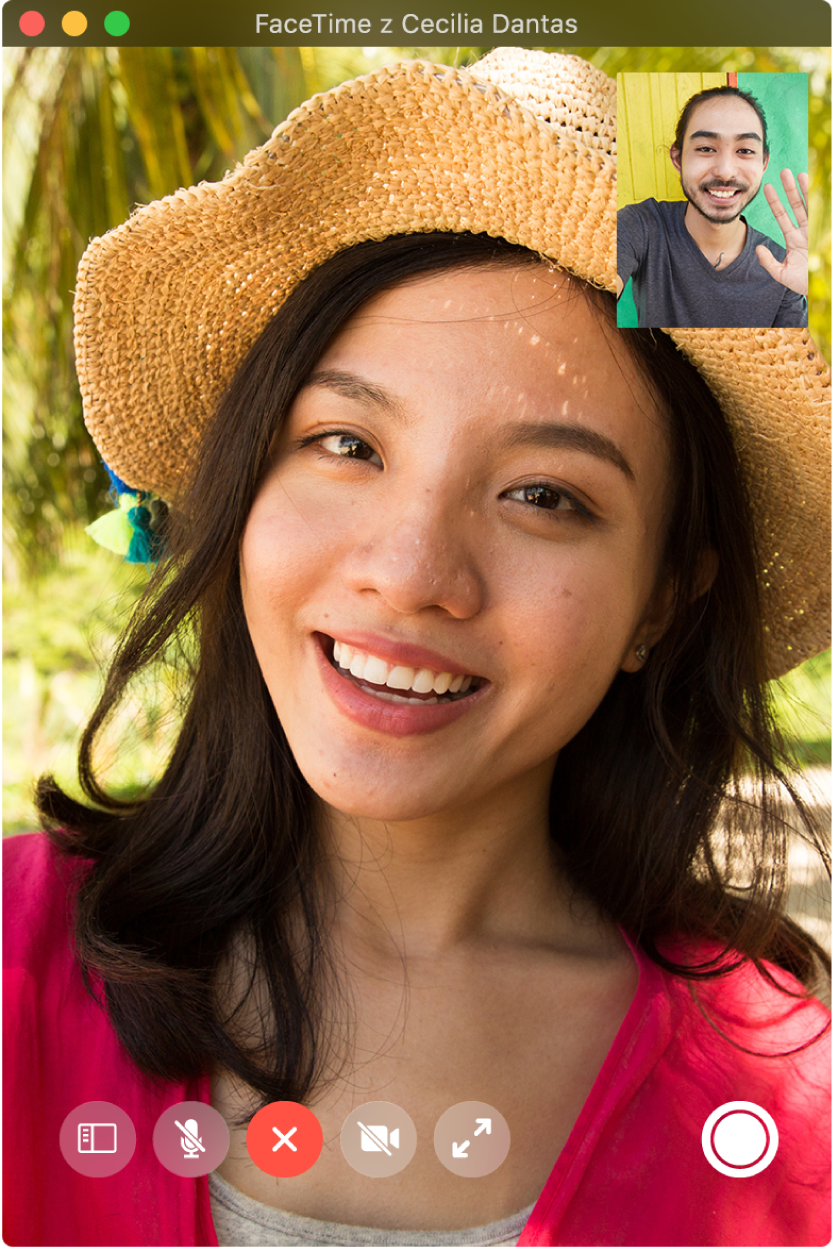Okno FaceTime wtrakcie połączenia między dwiema osobami; osoba, która zainicjowała połączenie, jest widoczna wmałym okienku wprawym górnym rogu. Wprawym dolnym rogu znajduje się przycisk LivePhoto, przy użyciu którego każda zosób może zachować dowolny moment rozmowy jako zdjęcie LivePhoto.