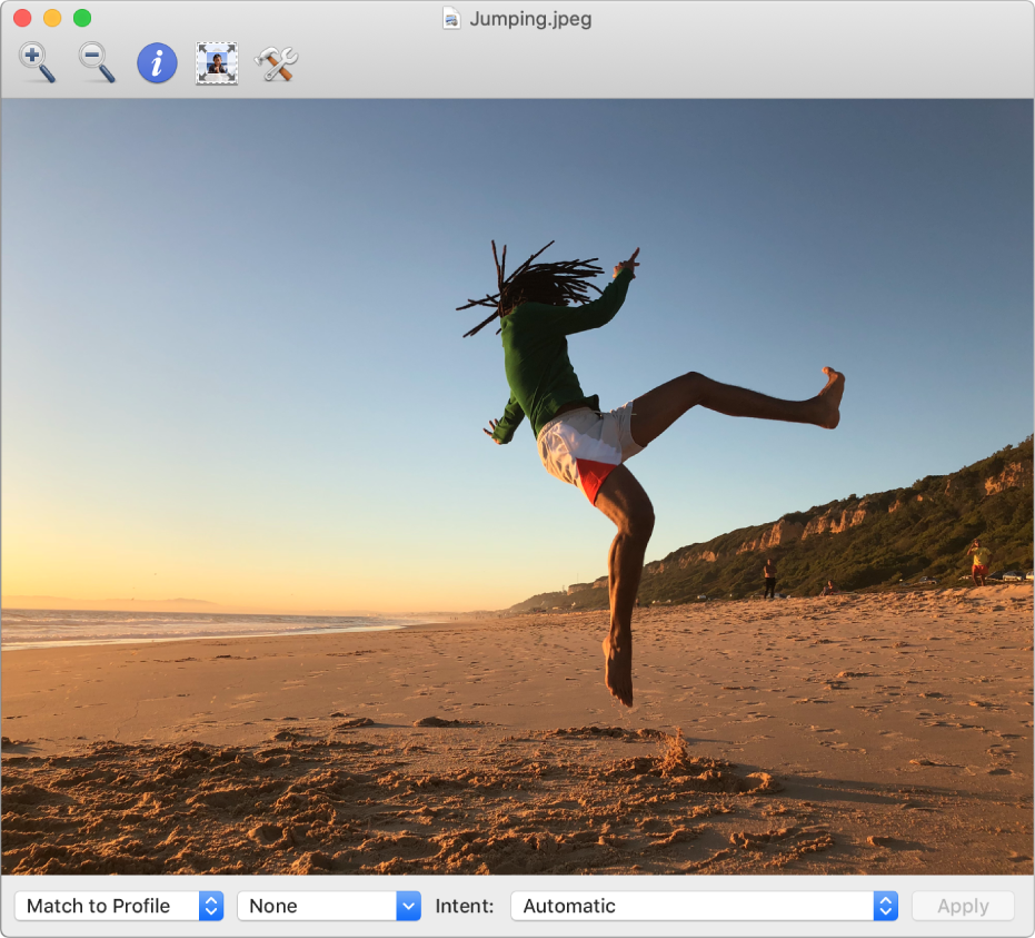 The ColorSync Utility window showing an image of a man jumping in the air on a beach.