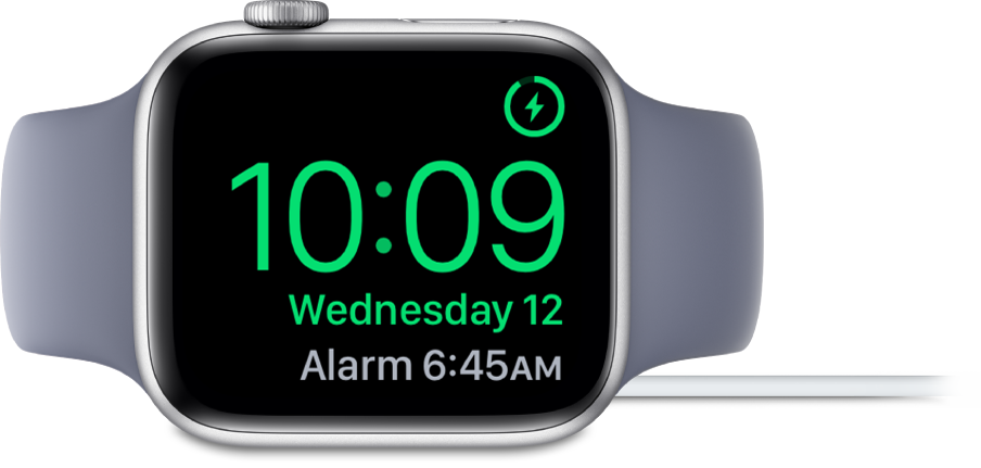 An Apple Watch placed on its side and connected to the charger, with the screen showing the charging symbol in the top-right corner, the current time below that, and the time of the next alarm.
