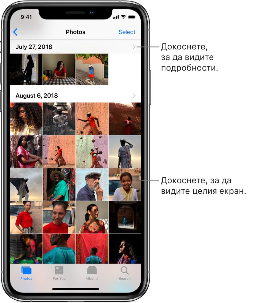 Приложението Photos (Снимки), в долния край на екрана от ляво надясно са етикетите Photos (Снимки), For You (За теб), Albums (Албуми) и Search (Търсене). Избран е етикетът Photos (Снимки) и екранът над него показва умалените изображения на снимките, подредени в групи по моменти. Над всеки момент е датата, на която са направени снимките. Докоснете датата, за да видите детайло за момента. Докоснете умалено изображение, за да видите снимката на пълен екран.