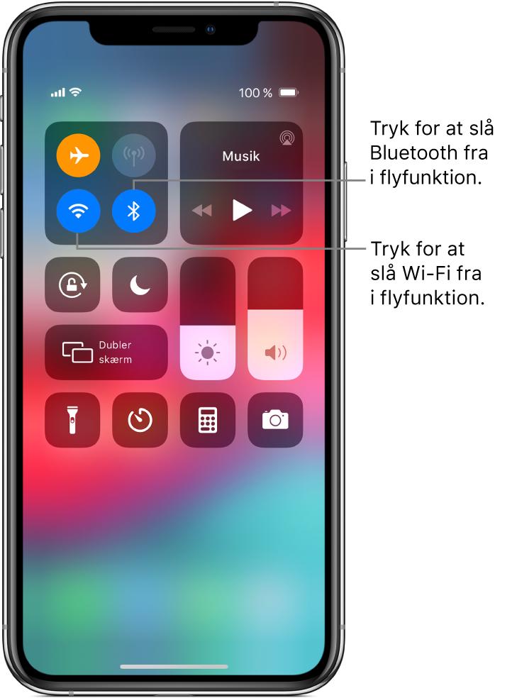 Kontrolcenter med flyfunktion slået til, med billedtekster, der forklarer, at hvis der trykkes på knappen nederst til venstre i den øverste venstre gruppe af betjeningsmuligheder, slås Wi-Fi fra, og hvis der trykkes på knappen nederst til højre i den pågældende gruppe, slås Bluetooth fra.