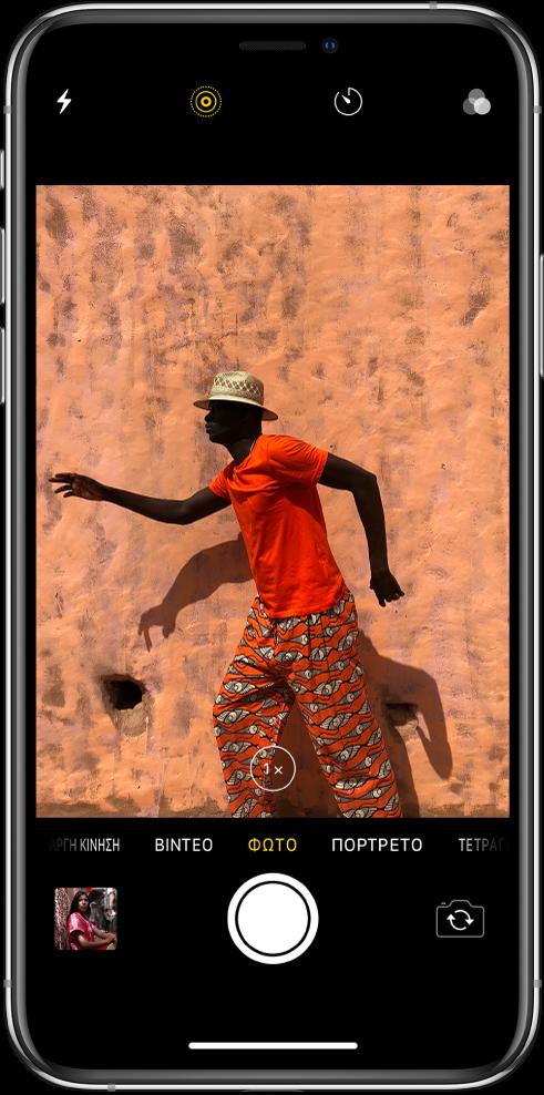 Η Κάμερα σε λειτουργία Φωτογραφίας, με τις άλλες λειτουργίες να φαίνονται αριστερά και δεξιά, κάτω από το εικονοσκόπιο. Τα κουμπιά για Φλας, Live Photo, Χρονοδιακόπτη και Φίλτρα εμφανίζονται στο πάνω μέρος της οθόνης. Μια μικρογραφία εικόνας κάτω αριστερά επιτρέπει την πρόσβαση σε υπάρχουσες φωτογραφίες και βίντεο. Το κουμπί «Κλείστρο» βρίσκεται κάτω στο κέντρο και το κουμπί «Αλλαγή κάμερας» βρίσκεται κάτω δεξιά.