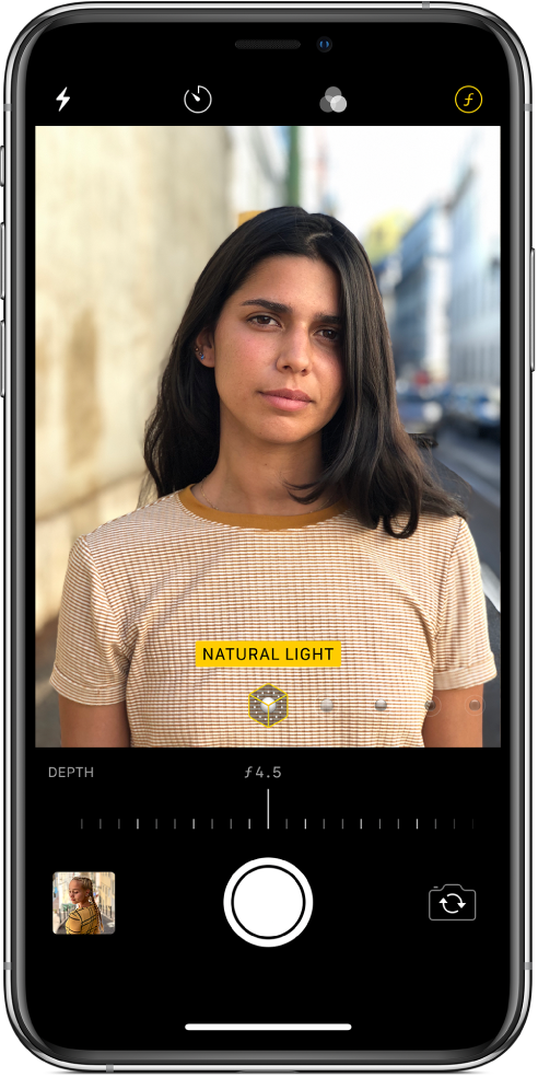 The Camera screen in Portrait mode. The Depth Adjustment button in the top right corner of the screen is selected. In the camera viewer, a box shows that the Portrait Lighting option is set to Natural Light, and there's a slider to change the lighting option. Below the camera viewer, there is a slider to adjust the Depth Control.