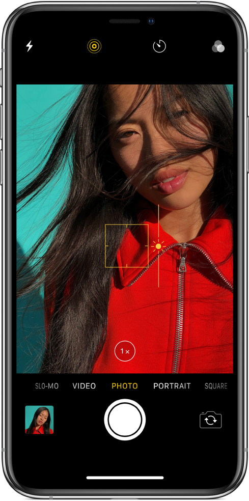 The Camera screen in Photo mode. In the viewer, an outline of a yellow box shows the area of focus, and a slider can be dragged up or down to adjust the exposure. The 1x Zoom button can be used to zoom in.