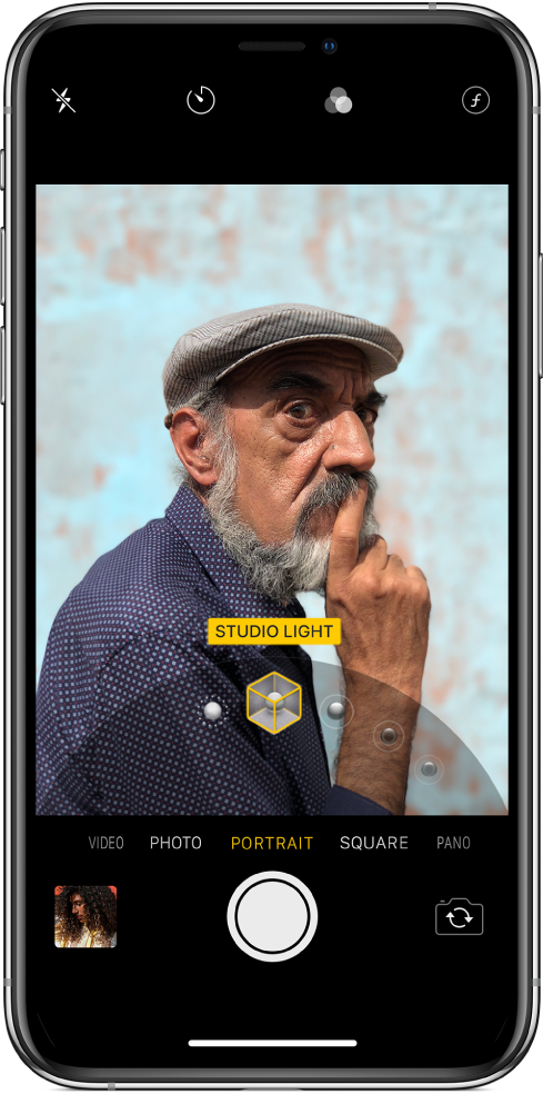 The Camera screen with Portrait mode selected. In the viewer, a box shows that the Portrait Lighting option is set to Studio Light, and there's a slider to change the studio lighting option.