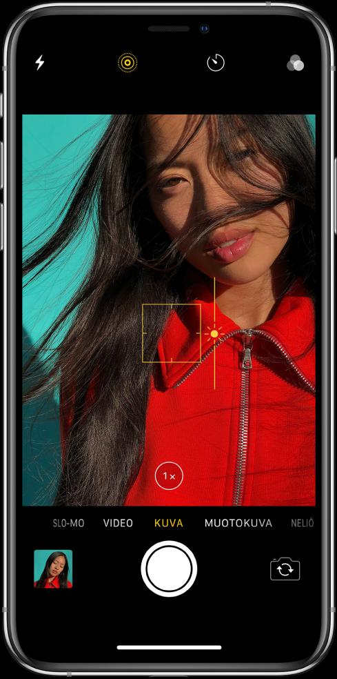 Kameran näyttö Kuva-tilassa. Näkymässä keltaisen laatikon ääriviivat osoittavat tarkennetun alueen, ja valotusta voidaan säätää vetämällä liukusäädintä ylös tai alas. 1x Zoom -painikkeella voidaan lähentää näkymää.