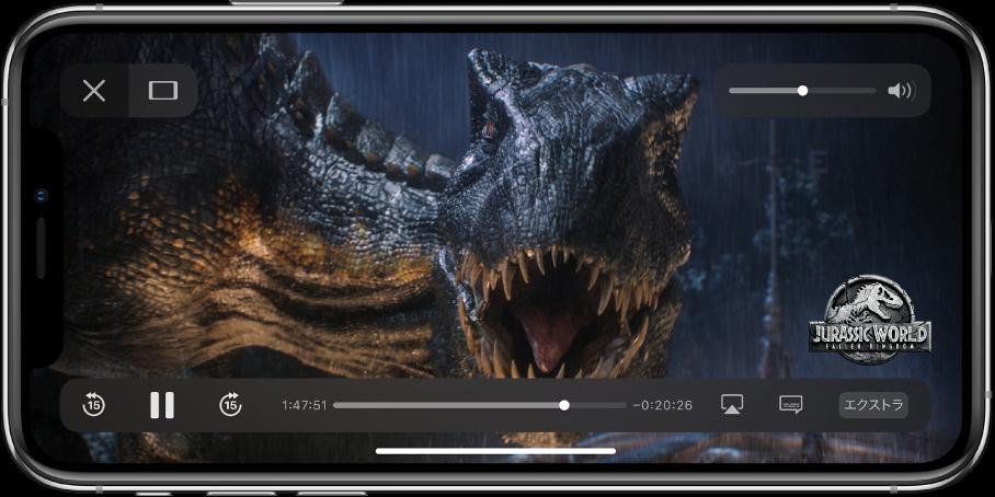 再生中の映画。再生コントロールが表示されています。左上に「完了」と「幅に合わせる」のボタンがあります。右上には音量スライダがあります。左下には15秒前にスキップ、一時停止、および15秒先にスキップのボタンがあります。下部中央にはビデオの位置をドラッグして調整できるスライダがあります。スライダの両端には経過時間と残り時間が表示されています。右下には、ビデオの再生出力先を変更するボタン、字幕を表示するボタン、追加コンテンツを再生するボタンがあります。