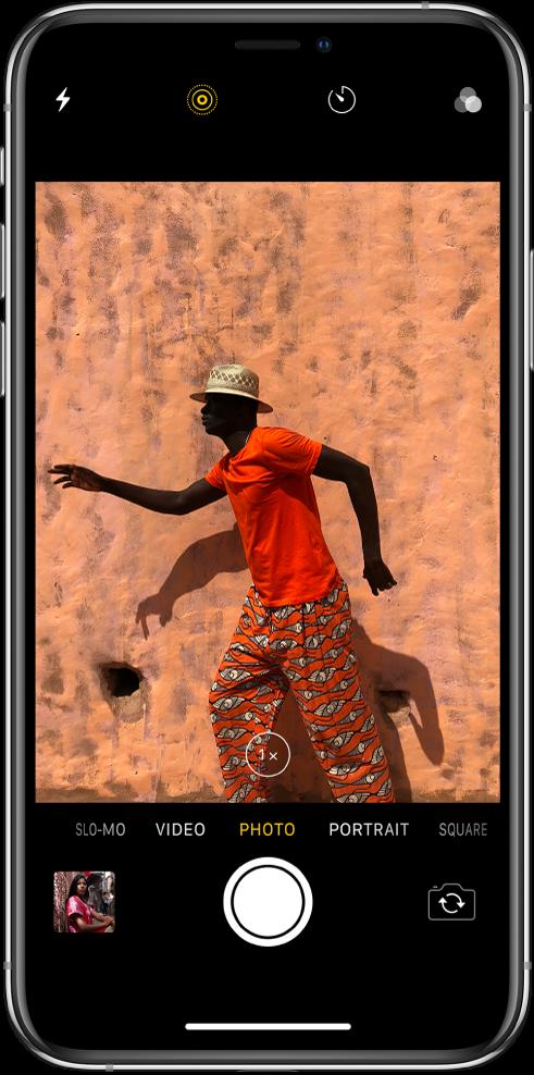 """Režimu """"Photo"""" veikianti programa """"Camera"""", kiti režimai pateikti kairėje ir dešinėje po žiūrykle. Ekrano viršuje atsiranda """"Flash"""", """"Live Photo"""", """"Timer"""" ir """"Filters"""" mygtukai. Apatiniame kairiajame kampe esantis miniatiūros vaizdas suteikia galimybę peržiūrėti turimus vaizdo įrašus ir nuotraukas. """"Shutter"""" mygtukas yra apačioje centre, o """"Switch Camera"""" mygtukas – apačioje dešinėje."""