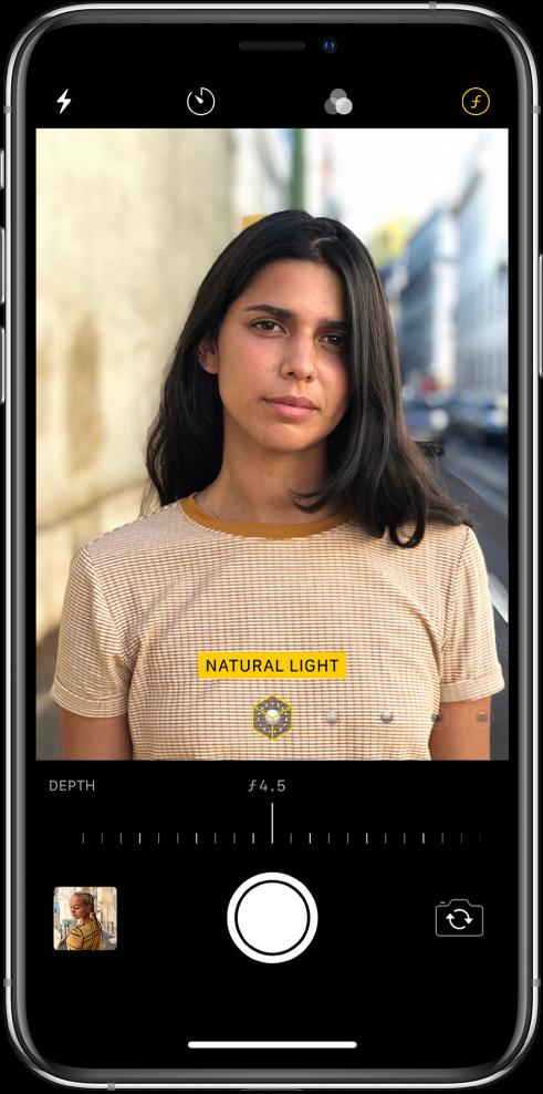 """""""Camera"""" ekranas naudojant """"Portrait"""" režimą. Pasirinktas """"Depth Adjustment"""" mygtukas viršutiniame dešiniajame ekrano kampe. Kameros vaizdo ieškiklyje rodoma, kad """"Portrait Lighting"""" apšvietimo parinktis nustatyta kaip """"Natural Light"""" apšvietimas, o apšvietimą galite pakeisti slankikliu. Žemiau kameros vaizdo ieškiklio yra """"Depth Control"""" reguliavimo slankiklis."""