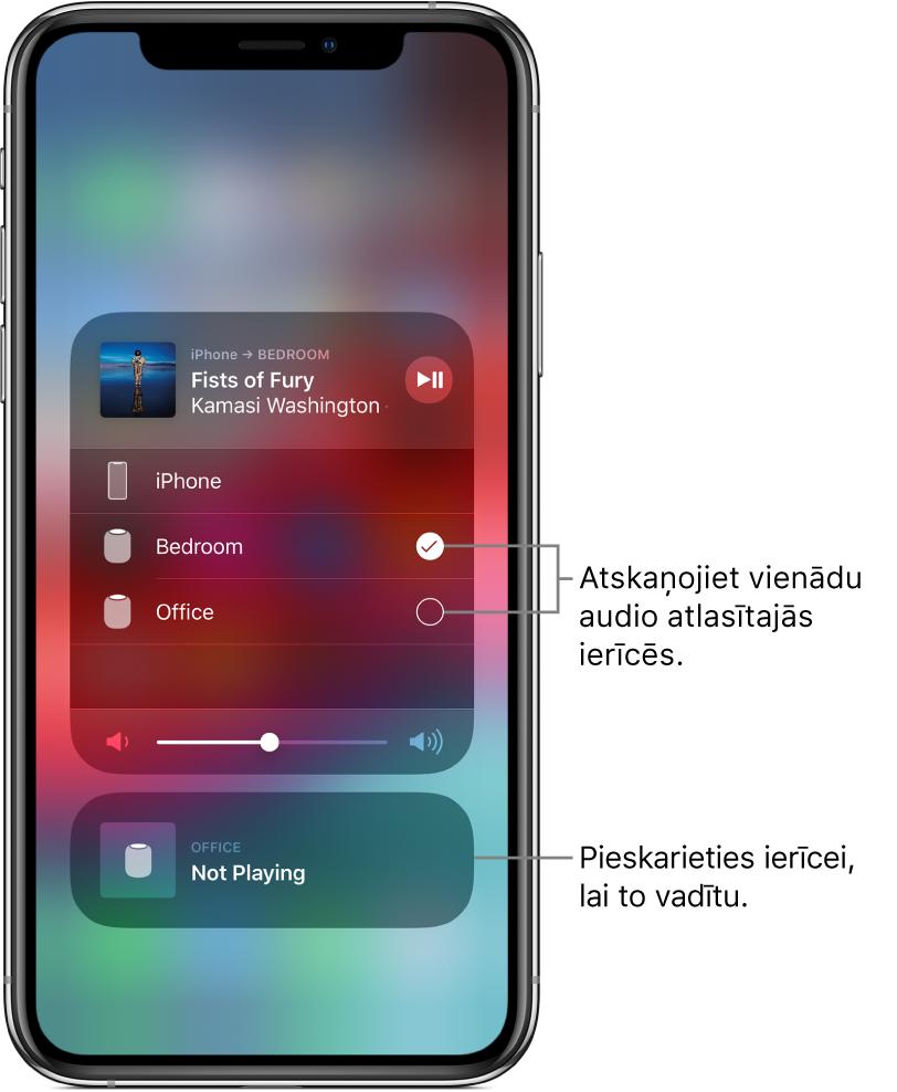 """AirPlay ekrāns, kurā parādītas divas kartītes. Augšpusē atrodas atvērta iPhone audio kartīte, kurā ir norādīts dziesmas nosaukums un izpildītājs. Šajā kartītē ir redzami divi skaļruņi— viesistabā un guļamistabā—, un ir atlasīts guļamistabas skaļrunis. Uz diviem skaļruņiem norāda remarka """"Play the same audio on selected devices"""". Atvērtās kartītes apakšdaļā ir redzams skaļuma slīdnis. Ekrāna apakšdaļā atrodas aizvērta kartīte, kura attiecas uz biroja skaļruni. Tai ir norāde Not Playing. Uz apakšējo aizvērto kartīti norāda remarka """"Tap a device to control it""""."""