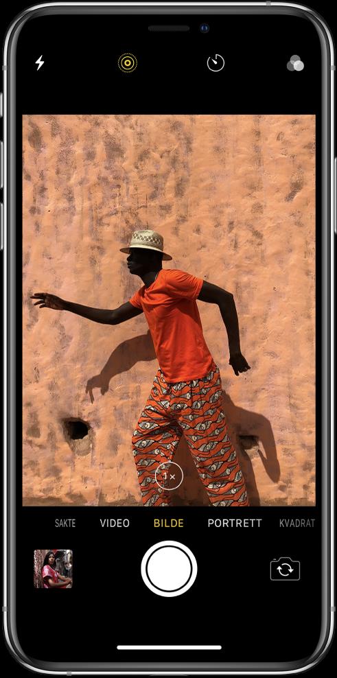 Kamera i Bilde-modus med andre moduser til venstre og høyre under bildevisningen. Knapper for blits, Live Photo, Nedtelling og filtre vises øverst på skjermen. Et miniatyrbilde nede til venstre gir tilgang til eksisterende bilder og videoer. Utløserknappen er nederst i midten, og Bytt kamera-knappen er nede til høyre.