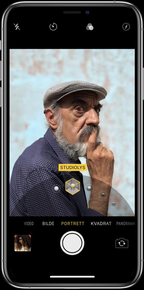 Kamera-skjermen, med Portrett-modus valgt. En rute i bildevisningen viser at Studiolys er valgt for Portrettlyssetting, og det er en skyveknapp for å endre lyssettingsvalget.