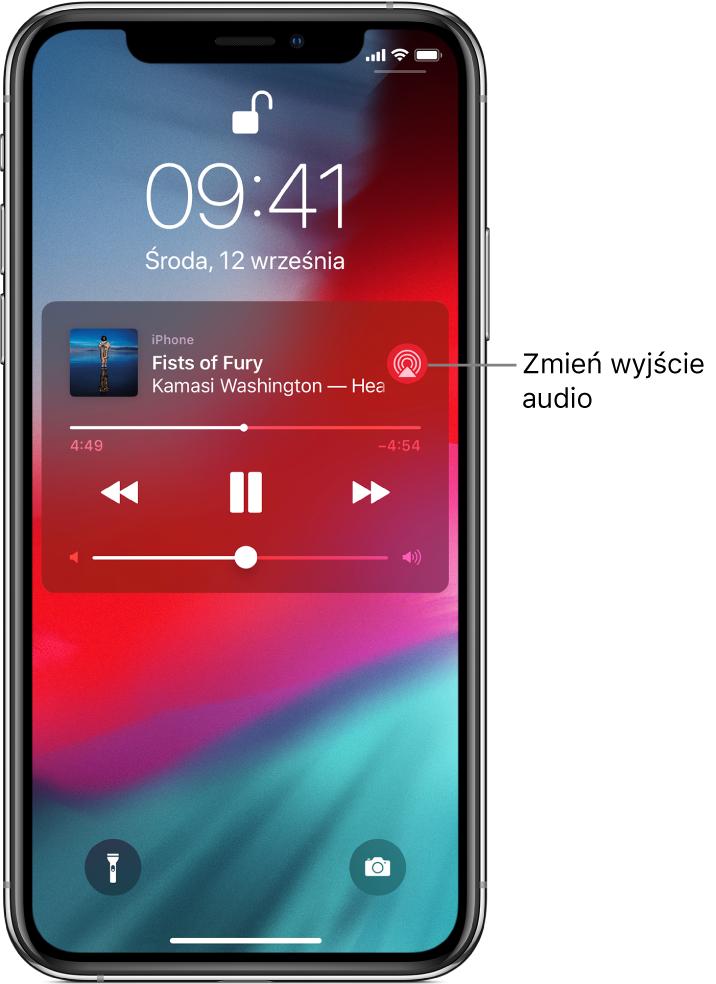 Zablokowany ekran zawierający odtwarzany utwór, narzędzia sterowania odtwarzaniem oraz przycisk Odtwarzanie przez.