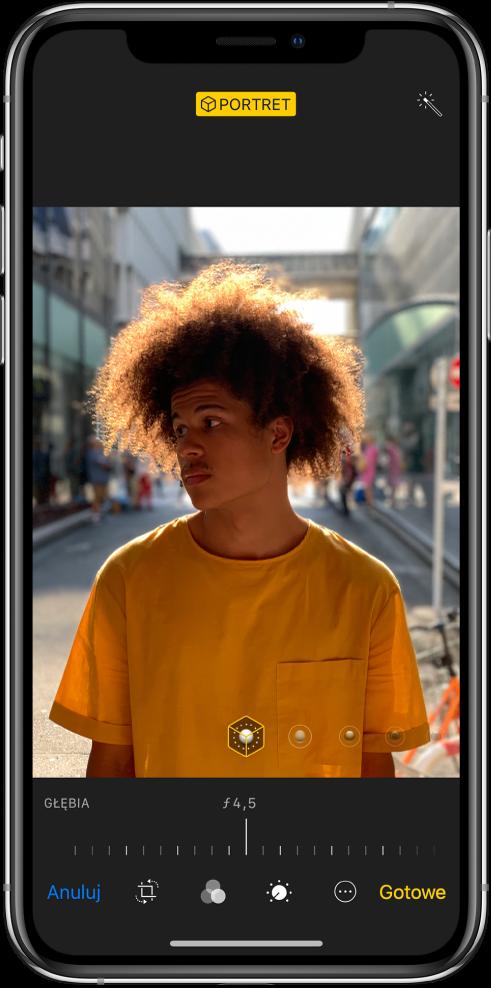Ekran edycji zdjęcia zrobionego wtrybie Portret. Na środku ekranu znajduje się zdjęcie. Pod zdjęciem wyświetlany jest suwak pozwalający zmieniać siłę efektu głębi. Pod suwakiem (od lewej do prawej) znajdują się przyciski anulowania, kadrowania, filtrów, minutnika, Więcej iGotowe.