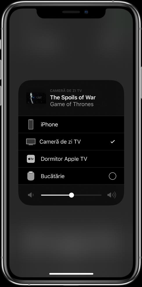 O fereastră AirPlay este deschisă și prezintă titlul unui episod dintr-o emisiune TV. Dedesubt este o listă de dispozitive AirPlay. Este selectat televizorul din living. Un glisor de volum se află în partea de jos a ferestrei.