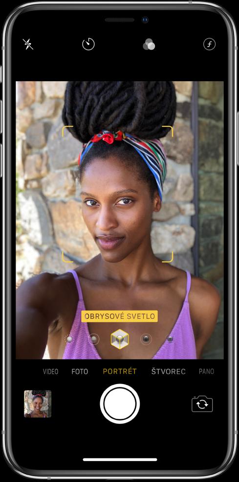 Obrazovka apky Kamera svybraným režimom Portrét. Vhľadáčiku sa vobdĺžniku zobrazuje, že možnosť osvetlenia portrétu je nastavená na Obrysové svetlo, anachádza sa tam posuvník na zmenu osvetlenia.