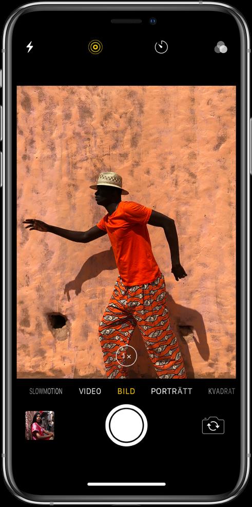 Kamera i bildläget med andra lägen till vänster och höger under sökaren. Knappar för blixt, LivePhoto, timer och filter visas högst upp på skärmen. En bildminiatyr längst ned till vänster som ger tillgång till befintliga bilder och videor. Du hittar slutarknappen längst ned i mitten och knappen för att byta kamera längst ned till höger.