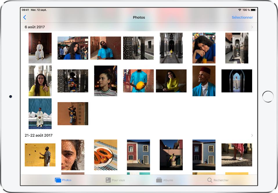 L'app Photos en orientation paysage. En bas de l'écran, de gauche à droite, se trouvent les onglets Photos, Pourvous, Albums et Rechercher. L'onglet Photos est sélectionné et l'écran au-dessus affiche une grille de vignettes de photo regroupées en moments. Au-dessus de chaque moment se trouve la date à laquelle les photos ont été prises. Touchez la date pour afficher les détails du moment. Touchez la vignette d'une photo pour afficher celle-ci en plein écran.