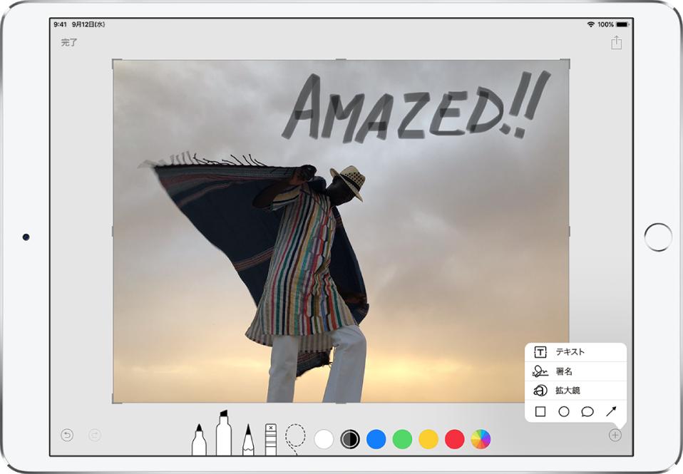 写真に灰色の手書きの文字で「すごい!」という注釈が付けられています。画面の下部には描画ツールと色の選択肢が表示されています。右下隅には、テキスト、署名、拡大鏡、シェイプの追加を選択できるメニューが表示されています。