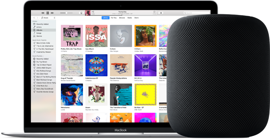 A MacBook with iTunes on the screen and a HomePod nearby.