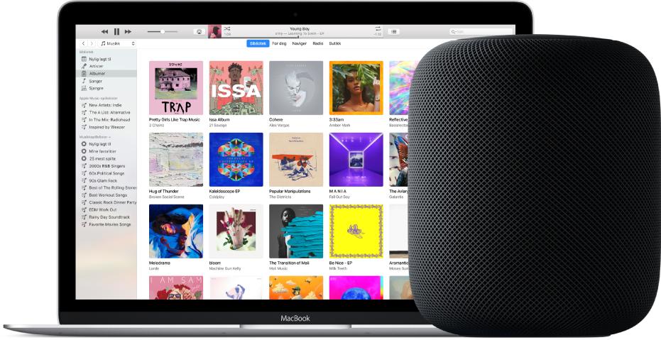 En MacBook med iTunes på skjermen og en HomePod i nærheten.