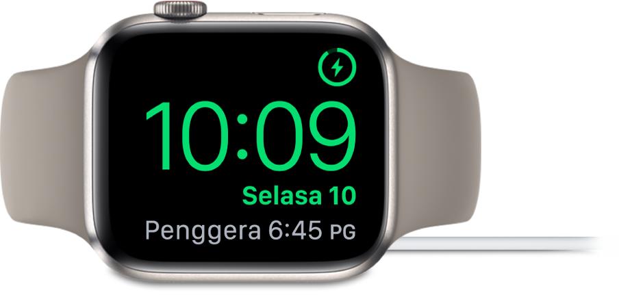 Apple Watch diletakkan di sisi dan bersambung ke pengecas, dengan skrin menunjukkan simbol mengecas di penjuru atas kanan, masa semasa di bawahnya dan penggera di sebelahnya.