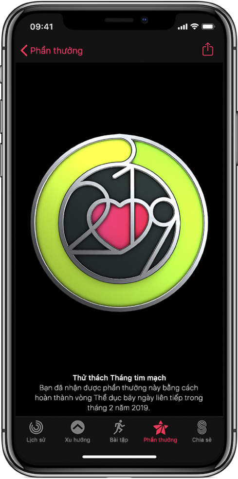 Tab Phần thưởng của màn hình ứng dụng Hoạt động trên iPhone, đang hiển thị một phần thưởng thành tích ở giữa màn hình. Bạn có thể kéo để xoay phần thưởng. Nút Chia sẻ ở trên cùng bên phải.