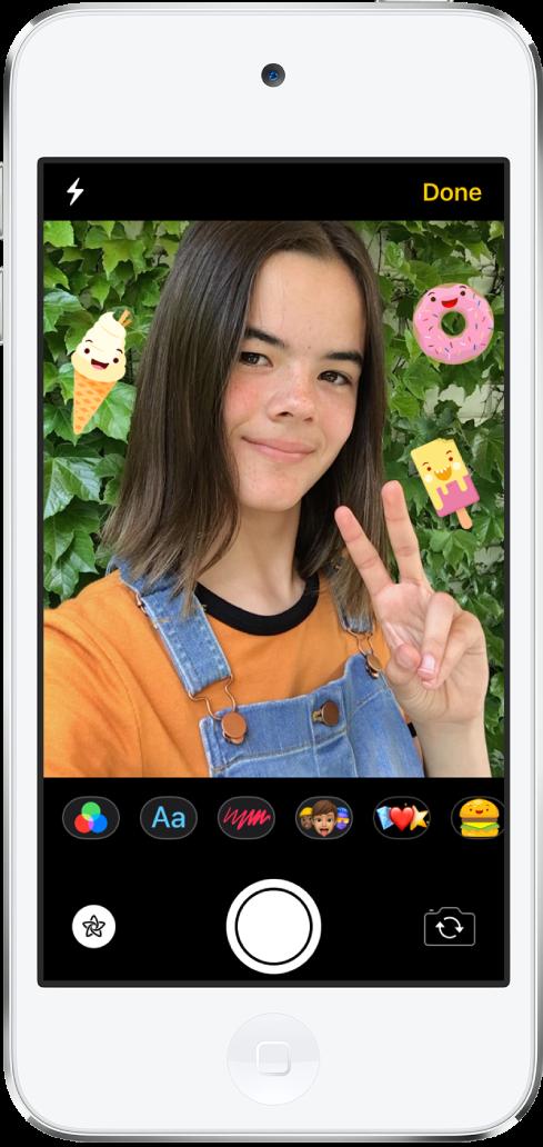 """""""信息""""效果屏幕。屏幕顶部显示前置摄像头取景框。iMessage 信息贴纸围绕在取景框中的主体周围。取景框下方从左到右依次是滤镜、文本、形状、拟我表情和动话表情按钮。屏幕底部从左到右依次是""""效果""""、""""快门""""和""""摄像头选取器""""按钮。"""