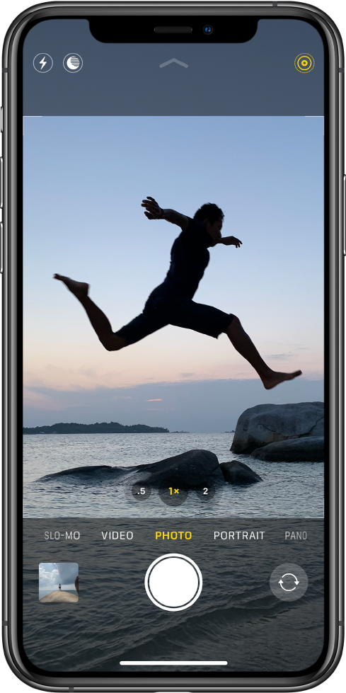 The Camera screen in Photo mode, with other modes to the left and right below the viewer. Buttons for Flash, Night mode, and Live Photo are at the top of the screen. Below the camera modes are, from left to right, an image thumbnail to access photos and videos, the Shutter button, and the Switch Camera button.