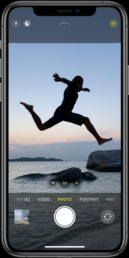 사진 모드의 카메라 앱 화면과 화면 보기 아래의 왼쪽부터 오른쪽으로 나열된 다른 모드들. 플래시, 야간 모드, LivePhoto 버튼이 화면 상단에 표시됨. 카메라 모드 아래에 사진과 비디오에 접근하기 위한 이미지 축소판, 셔터 버튼 및 카메라 전환 버튼이 왼쪽에서 오른쪽으로 나열됨.