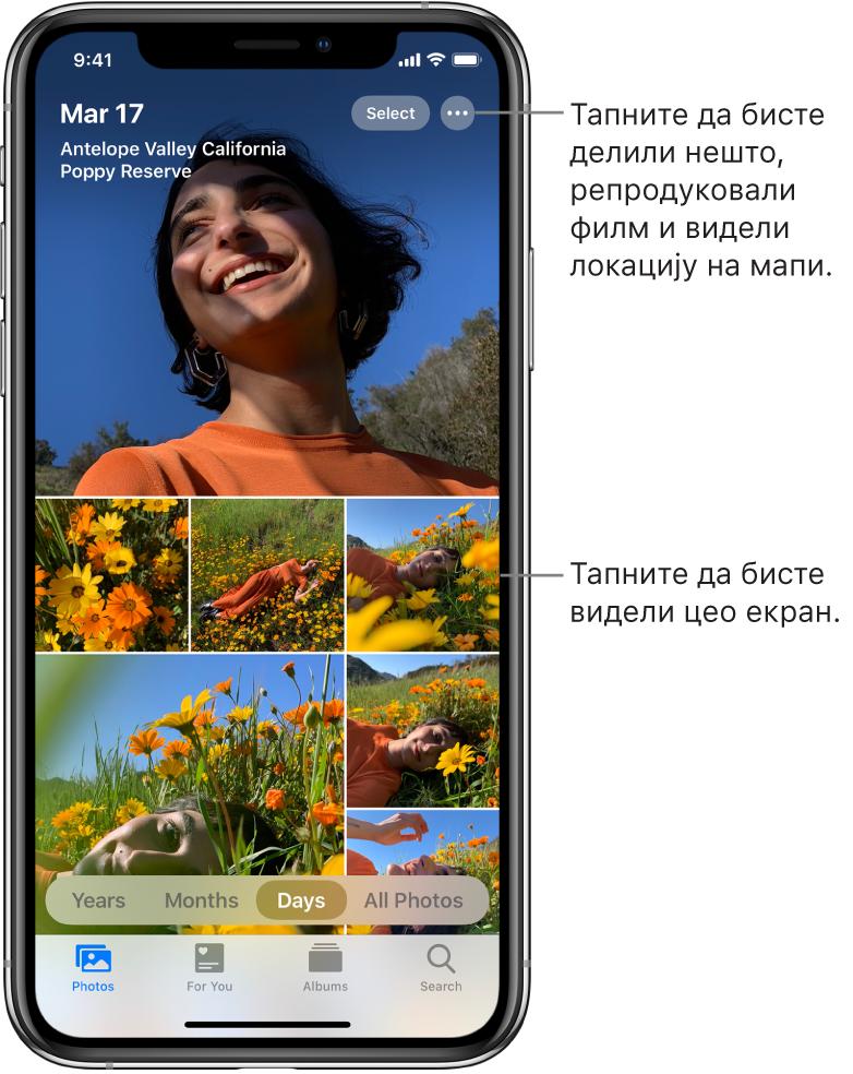 Библиотека фотографија приказана у приказу Days. Избор сличица фотографија попуњава екран. У горњем левом углу екрана су датум и локација где су снимљене фотографије. У горњем десном углу су дугмад Select и More Options за дељење фотографија и приказ детаља. Испод сличица су опције приказа библиотеке фотографија Years, Months, Days и All Photos. На дну су картице Photos, For You, Albums и Search.