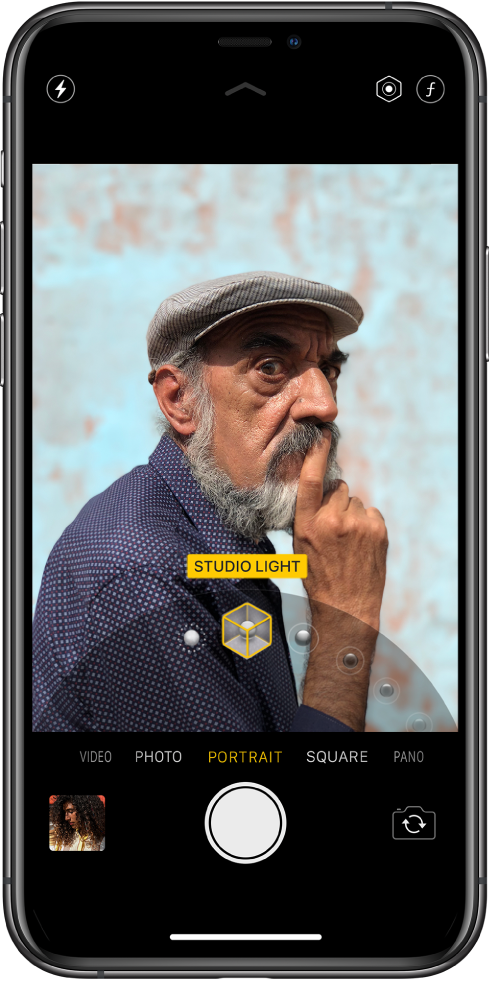 Екран Камери в режимі «Портрет»; об'єкт чіткий, а тло розмите. Унизу кадру відкрито диск для вибору ефектів портретного освітлення. Вибрано «Студійне світло». Угорі зліва екрана є кнопка «Спалах», а вгорі справа екрана— кнопки для налаштування інтенсивності портретного освітлення та керування глибиною. Унизу зліва направо розташовані мініатюра зображення для доступу до фотографій і відео, кнопка «Затвор» і кнопка «Перемикнути камеру».