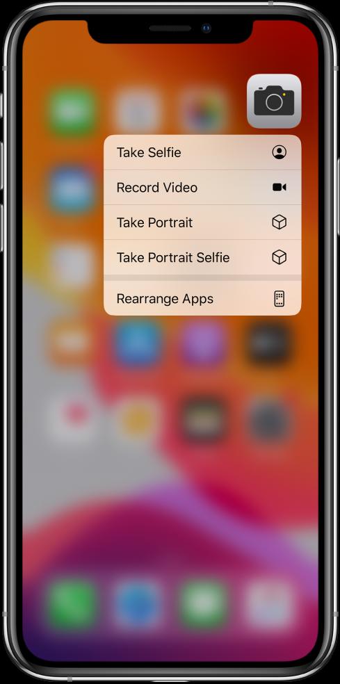 La pantalla de inicio difuminada, mostrando el menú de acciones rápidas de Cámara, debajo del ícono de la app.