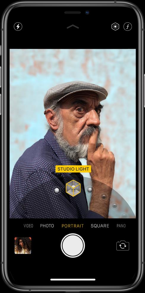 Екран апликације Camera у режиму Portrait. Субјект је изоштрен, а позадина замућена. Бројчаник за избор Portrait Lighting ефеката је отворен при дну оквира и изабран је ефекат Studio Light. У горњем левом углу екрана је дугме Flash, а у горњем десном углу екрана су дугмад за прилагођавање интензитета за Portrait Lighting и контроле дубине поља. Близу дна екрана се налазе, слева надесно, сличица снимка за приступ фотографијама и видео снимцима, дугме Shutter и дугме Switch Camera.