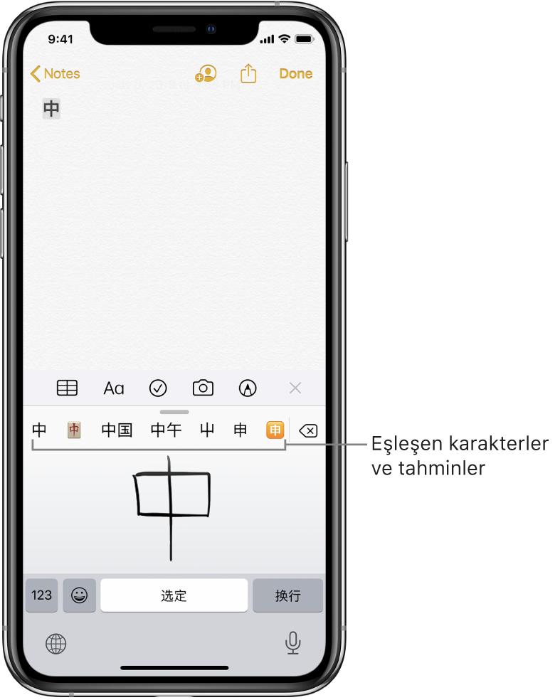 Ekranın alt yarısı dokunmatik ekranı gösterirken Notlar uygulaması. Dokunmatik ekranda elle çizilmiş bir Çince karakter bulunuyor. Notte önerilen karakterler hemen üstte ve seçilen karakter en üstte görüntüleniyor.