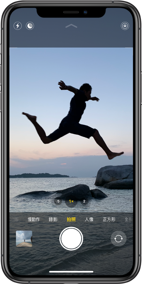 「相機」畫面處於「拍照」模式,其他模式位於觀景窗下方左右兩側。「閃光燈」、「夜間模式」和「原況照片」的按鈕位於螢幕最上方。相機模式下方從左到右則是取用照片和影片的影像縮覽圖、「快門」按鈕,以及「切換相機」按鈕。