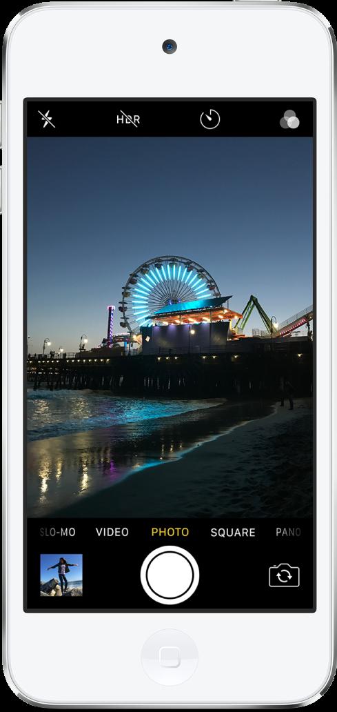 사진 모드의 카메라와 화면 보기 아래의 왼쪽부터 오른쪽으로 나열된 다른 모드들. 화면 상단에 표시된 플래시, HDR, 타이머, 필터 버튼. 기존 사진과 비디오에 접근할 수 있는 하단 왼쪽의 이미지 축소판. 하단 중앙에 있는 셔터 버튼과 오른쪽 하단에 있는 카메라 전환 버튼.