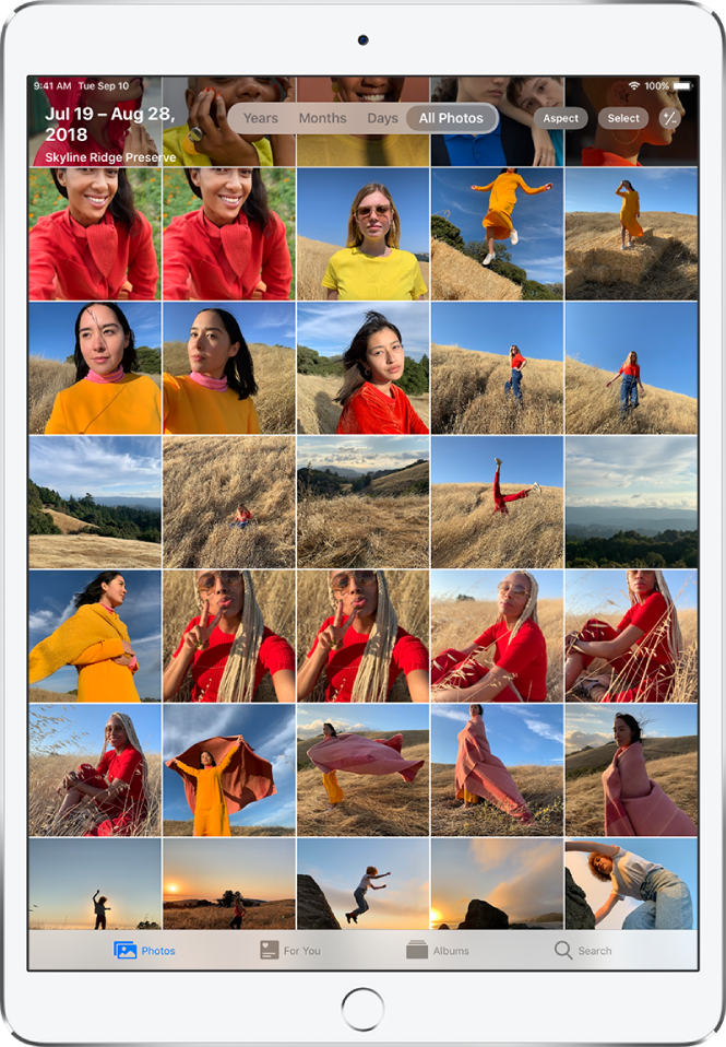 The Photos app. At the bottom of the screen from left to right are the Photos, For You, Albums, and Search tabs. The Photos tab is selected and a grid of photo thumbnails fills the screen. In the top left of the screen are the date and location where the photos were taken. In the top center are options to view photos by Years, Months, Days, and All Photos; All Photos is selected. In the top right of the screen are the Aspect, Select, and Zoom buttons.