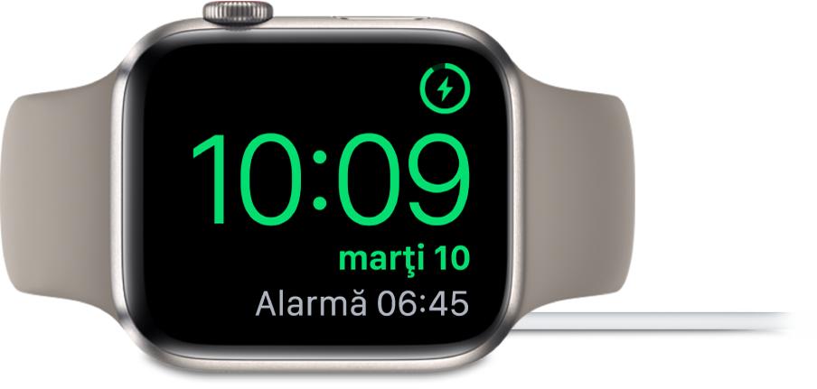 Un Apple Watch așezat pe muchie și conectat la încărcător, pe ecran fiind afișat simbolul de încărcare în colțul din dreapta sus, ora actuală dedesubt și ora alarmei următoare.