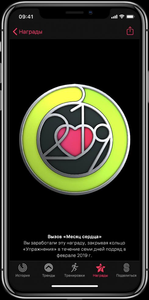Вкладка «Достижения» на экране программы «Активность» на iPhone. В центре экрана отображается награда за достижение. Вы можете поворачивать награду жестом перетягивания. Кнопка «Поделиться» расположена слева вверху.